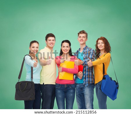 friendship, education and people concept - group of smiling teenagers with folders and school bags showing thumbs up over green board background - stock photo