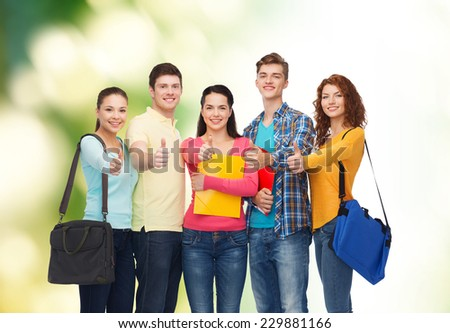 friendship, education, ecology and people concept - group of smiling teenagers with folders and school bags showing thumbs up over green background - stock photo
