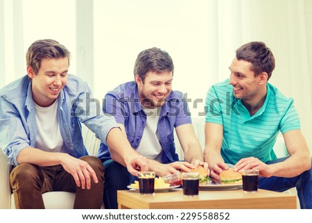 friendship, food and leisure concept - smiling friends with soda and hamburgers at home - stock photo
