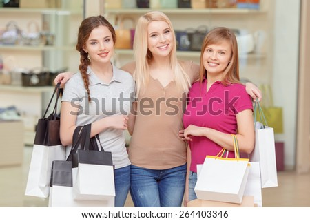 Friendship forever. Three beautiful girls smiling and watching at a camera hold shopping bags copyspace with a store on the background - stock photo