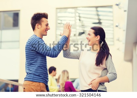 friendship, gesture, education and people concept - group of smiling students outdoors making high five - stock photo