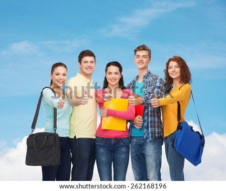 friendship, gesture, education and people concept - group of smiling teenagers with folders and school bags showing thumbs up over blue sky with white cloud background - stock photo