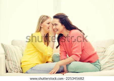 friendship, gossip and happiness concept - one girl telling another secret - stock photo