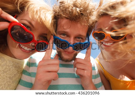 Friendship happiness summer freedom concept. Group of friends boy two girls in colorful sunglasses having fun outdoor, joy playful mood, wide angle view