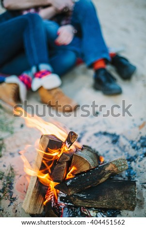 Friendship, happiness, summer vacation, holidays and people concept - fire on beach and couple sitting on background out of focus. - stock photo