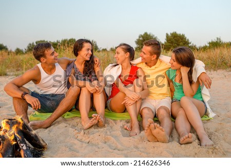 friendship, happiness, summer vacation, holidays and people concept - group of smiling friends sitting near fire on beach - stock photo