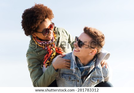 friendship, leisure, international, freedom and people concept - happy teenage couple in shades having fun outdoors - stock photo