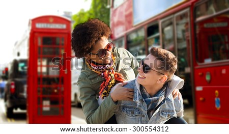 friendship, leisure, international, freedom and people concept - happy teenage couple in shades having fun over london city street background - stock photo