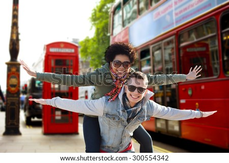 friendship, leisure, international, freedom and people concept - happy teenage couple in shades having fun over london city bus on street background - stock photo