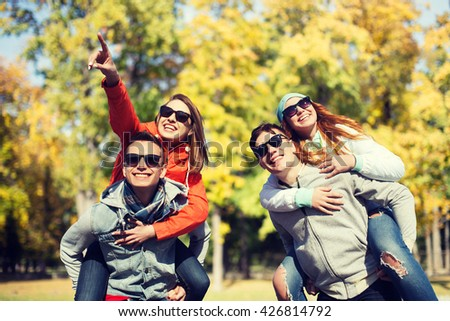 friendship, leisure, season and people concept - group of happy teenage friends in sunglasses having fun over autumn park background - stock photo