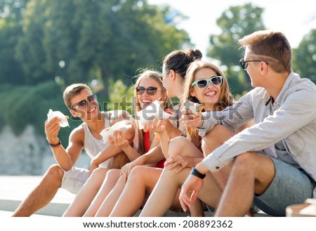 friendship, leisure, summer and people concept - group of smiling friends in sunglasses sitting with food on city square - stock photo