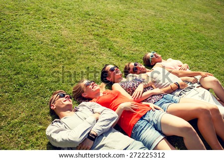 friendship, leisure, summer and people concept - group of smiling friends lying on grass outdoors - stock photo