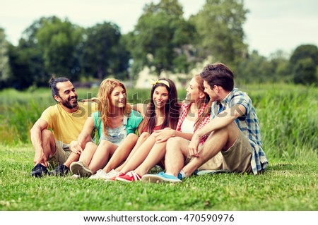 friendship, leisure, summer and people concept - group of smiling friends sitting on grass and talking outdoors