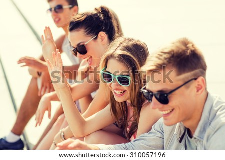 friendship, leisure, summer, gesture and people concept - group of laughing friends sitting on city square - stock photo