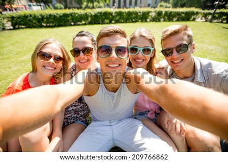 friendship, leisure, summer, technology and people concept - group of smiling friends making selfie with smartphone camera or tablet pc in park - stock photo