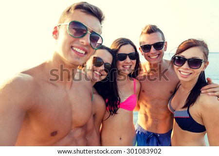 friendship, leisure, summer, technology and people concept - group of smiling friends making selfie on beach