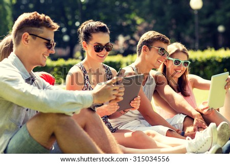 friendship, leisure, summer, technology and people concept - group of smiling friends with tablet pc computers and smartphone sitting on grass in park