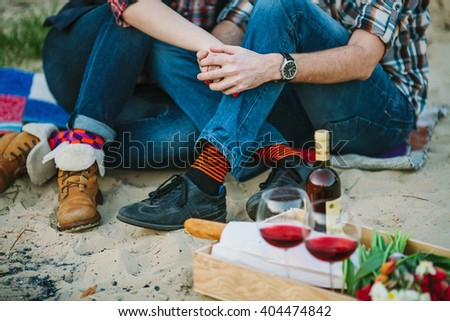 Friendship, love, happiness, summer vacation, holidays and people concept -couple sitting on beach and holding hands near bonfire. Shallow focus. - stock photo