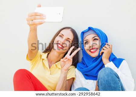 friendship of the religions concept: muslim and christian girl together - stock photo