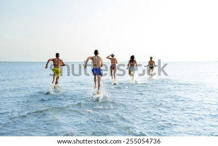 friendship, sea, summer vacation, holidays and people concept - group of smiling friends in swimwear running on beach from back - stock photo