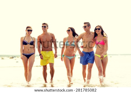 friendship, sea, summer vacation, holidays and people concept - group of smiling friends wearing swimwear and sunglasses walking on beach - stock photo