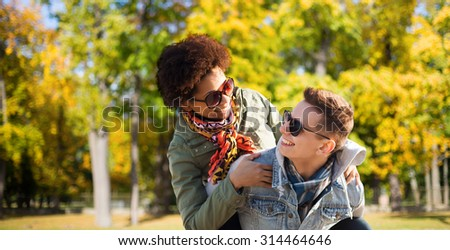 friendship, season, international and people concept - happy teenage couple in shades having fun over autumn park background - stock photo