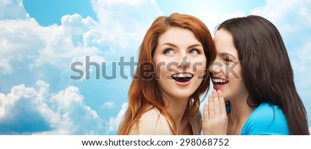 friendship, secrecy and people concept - two smiling girls or young women whispering gossip over blue sky with clouds background - stock photo