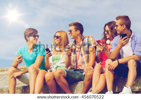 friendship, summer, technology and people concept - group of smiling friends with smartphones and headphones outdoors