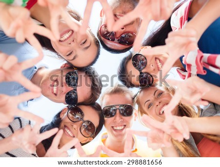 friendship, summer vacation, holidays and people concept - group of smiling friends showing victory gesture in circle over blue sky - stock photo