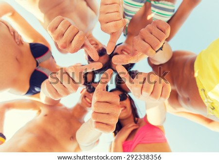 friendship, summer vacation, holidays, gesture and people concept - close up of smiling friends wearing swimwear standing in circle and showing thumbs up over blue sky - stock photo