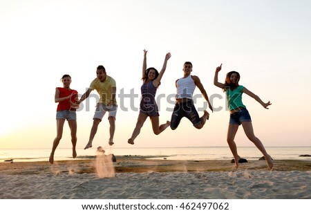 friendship, summer vacation, holidays, party and people concept - group of smiling friends dancing and jumping on beach