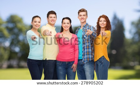 friendship, summer vacation, nature and people concept - group of smiling teenagers pointing finger on you over green park background - stock photo