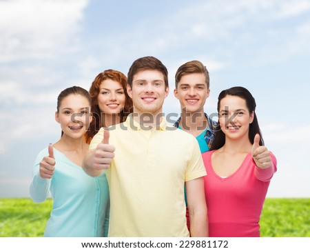 friendship, summer vacation, nature and people concept - group of smiling teenagers standing over blue sky and grass background - stock photo