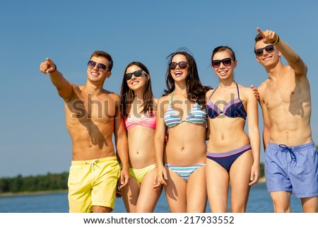 friendship, summer vacation, sea, gesture and people concept - group of smiling friends wearing swimwear and sunglasses walking and pointing finger on beach - stock photo