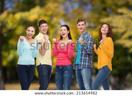 friendship, summer vacation, teamwork, gesture and people concept - group of smiling teenagers showing triumph gesture over green park background