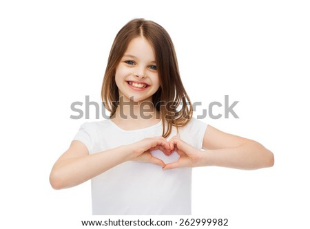 friendship, t-shirt design and happy people concept - smiling little girl in white blank t-shirts showing heart with hands - stock photo