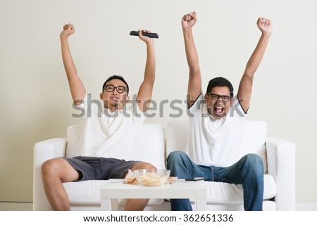 Friendship, technology and home concept. Happy male friends with remote control and junk food at home. - stock photo