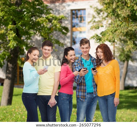 friendship, technology, education, school and people concept - group of smiling teenagers with smartphones over campus background