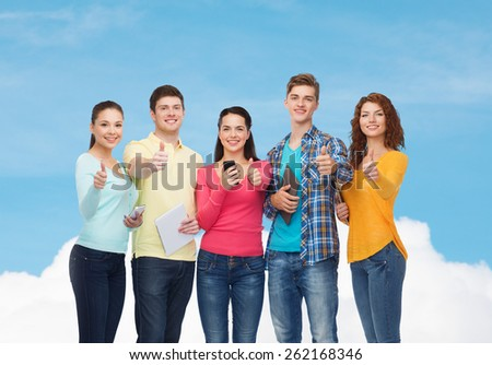 friendship, technolpgy and people concept - group of smiling teenagers with smartphones and tablet pc computers showing thumbs up over blue sky with white cloud background - stock photo