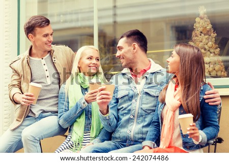 friendship, travel, drink and vacation concept - group of smiling friends with take away coffee - stock photo
