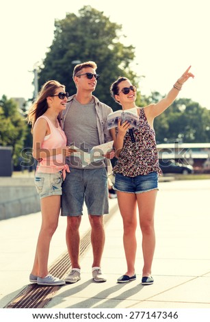 friendship, travel, tourism, vacation, summer and people concept - smiling friends with map and city guide pointing finger outdoors - stock photo