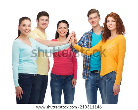 friendship, youth and people concept - group of smiling teenagers making high five