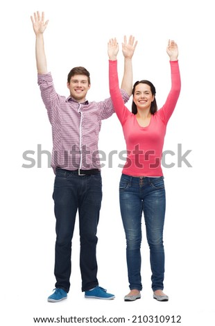 friendship, youth, greeting and people - smiling teenagers with raised hands