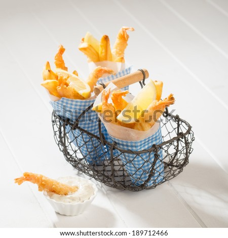 Fries and tempura prawns in a basket with tartar sauce on the side - stock photo