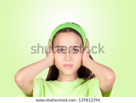 Frightened girl covering her ears isolated on a green background - stock photo