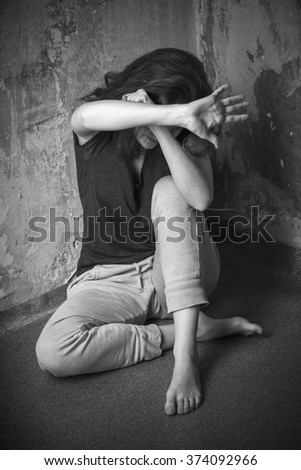 Frightened girl huddled in a corner of the room, his hands defensively - stock photo