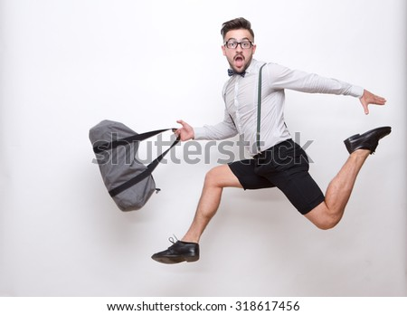 Frightened hipster man jumping with his bag over white. Bearded man in glasses looking as if he is in a hurry in photo studio. - stock photo