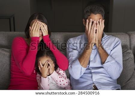 Frightened Hispanic Family Sitting On Sofa And Watching TV - stock photo