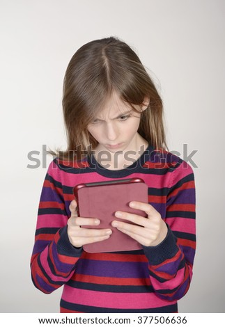 frightened little girl with digital tablet - stock photo
