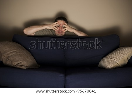 Frightened man hides behind couch while watching horror movie - stock photo